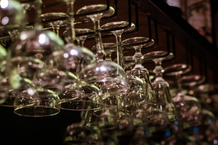 Empty cocktail and wine glasses on bar interior background. Artificial lighting creates reflections and glares in glass. Selective focus in center of image.