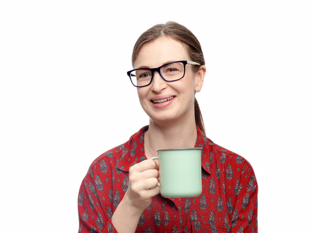 A portrait of pretty smiling young brunette woman with delicate makeup sitting on white background. She holding a cup with tea or coffee in right hand. Horizontal studio image with high resolution. 스톡 콘텐츠