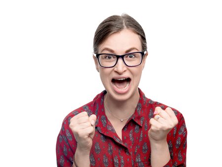 A portrait of young brunette woman screaming loudly. She looking at camera and her hands clenched fists. Horizontal image isolated on white background. 스톡 콘텐츠