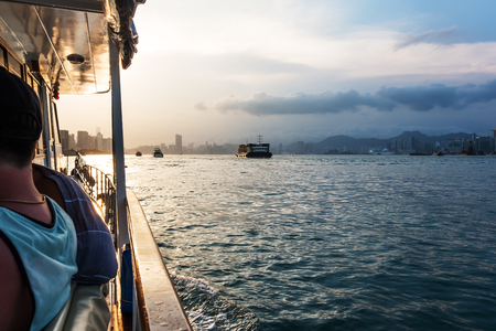 Pleasure boat moving across Victoria harbour at sunset. Hong Kong Island on background. People having fun. Wonderful weekend activities for friends. Perfect family getaway. Travel to Asia. 스톡 콘텐츠
