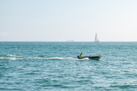 Motor boat moving fast in open sea with foam trace behind. Unrecognizable person in the boat. Sailboat on horizon line. Sunny day. Tropical vacation. Weekend getaway from city. Sport and recreational.