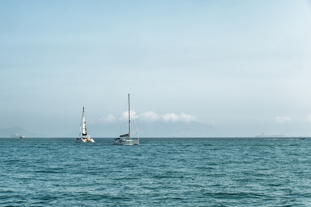 Luxury yachts in open sea at beautiful sunny day. Active lifestyle for active people. Tropical vacation. Weekend getaway from city. Natural landscape. Horizontal image with space for text and design.