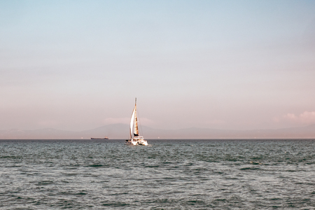 Luxury yacht with white sails in open sea at beautiful sunny day. Small waves on the sea and white clouds on horizon line. Weekend getaway from city. Wonderful world. Natural background.
