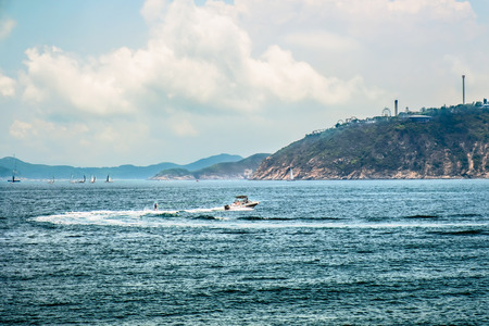 Motorboat moving fast on sea water surface with water skiing person behind. Mountains on background. Weekend getaway. Active lifestyle for active people. Tropical vacation. 版權商用圖片