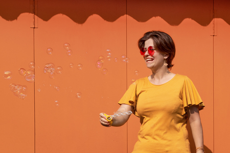 Beautiful young brunette woman in sunglasses having fun blowing soap bubbles. Metal texture orange color background. Happy person enjoying life. Positive emotion. Perfect smile. Outdoor activities.