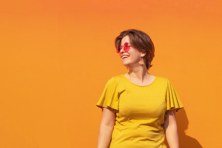 Beautiful young smiling woman wearing red sunglasses and yellow blouse standing on orange metal door. Happy girl having fun enjoying sunny day. Outdoor activities. Holiday or weekend spending time.