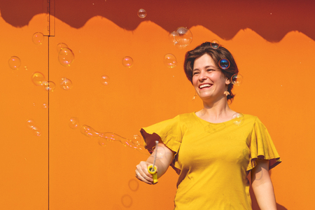 Beautiful young brunette woman having fun blowing soap bubbles. Metal texture orange color background. Happy person enjoying life. Positive emotion. Perfect smile. Outdoor activities.