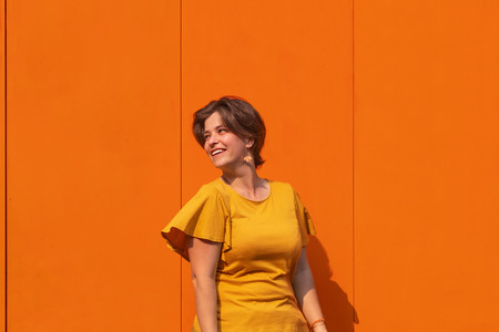 Attractive young smiling woman having fun in beautiful sunny day. Outdoor portrait of pretty brunette female model looking away of camera. Metal texture orange color wall on background. Head shot.