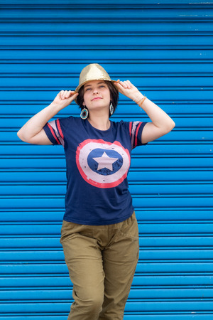 Beautiful young woman in golden hat standing near blue metal wall. Outdoor activities in sunny day. 스톡 콘텐츠