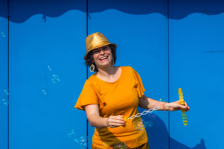 Beautiful young brunette woman wearing yellow blouse and bright golden hat blowing bubbles. Blue metal wall on background. Sunny day and high contrast between shadows and sun light. People having fun. 스톡 콘텐츠