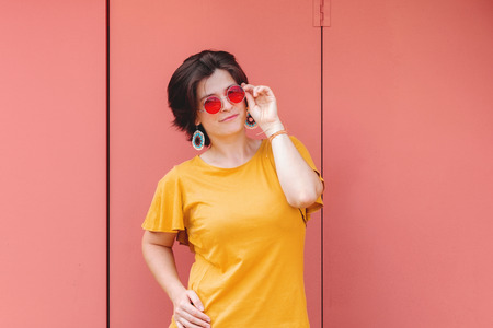 Young smiling woman in red sunglasses standing on metal texture pink color background. Pretty female person having fun in beautiful sunny day. Outdoor activities. Weekend or vacation spending time. 스톡 콘텐츠