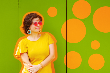 Beautiful young smiling woman wearing red sunglasses and yellow blouse standing on green colored metal texture background with decorative orange chalk board and circles in left side. 스톡 콘텐츠