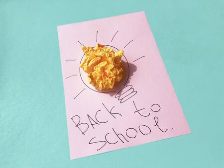 School studying, motivation, education concept. Crumpled yellow paper ball and drawing of lamp bulb on paper texture pink and blue colored background. Top view. Creative concept. 스톡 콘텐츠