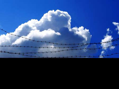 雲と青い空の上の黒いかみそりワイヤー 写真素材