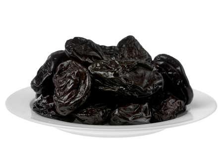 ciruela pasa: Detalle de plato de frutas secas de ciruela pasa en blanco