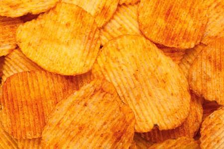 Orange pepper potato chips closeup textured background