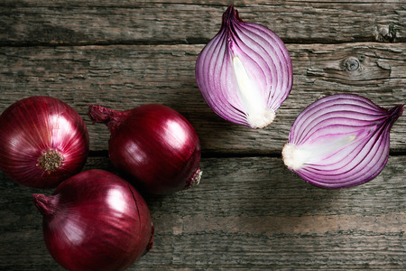 Fresh organic red onions on a wooden background