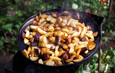 Beef meat stewed with potatoes on barbecue. Slice potatoes are prepared on the grill on sunny day. Close up. Culinary concept.