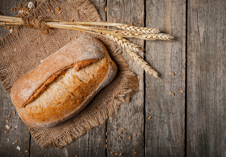 bread in rustic style retro background.Fresh traditional bread on wooden ground with flour in a sack