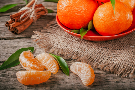 Tangerines with leaves and cinnamon stick on old wooden table. Stock fotó