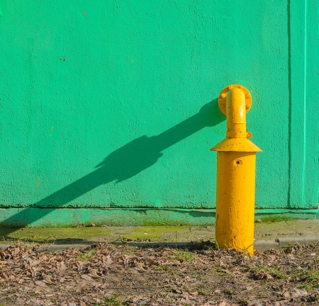 Yellow gas pipe in front of green building wall. Fragment of gas distribution station Stock Photo
