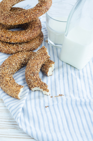 Turkish simit bagels with sesame, a bottle of milk and a glass on a wooden table. Cotton fabric and blur background
