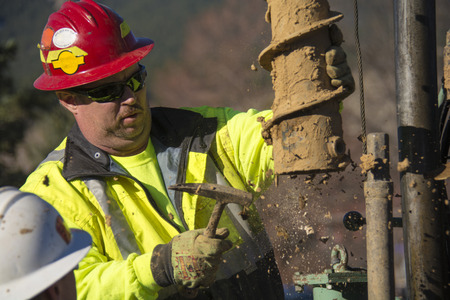 driller: A forman working on a drill rig  He is hammering some clay of the hollow stem auger Stock Photo