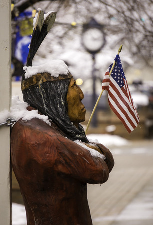 An indian figure outside a Golden Colorado mercantile store that is chained to a post and frozen.
