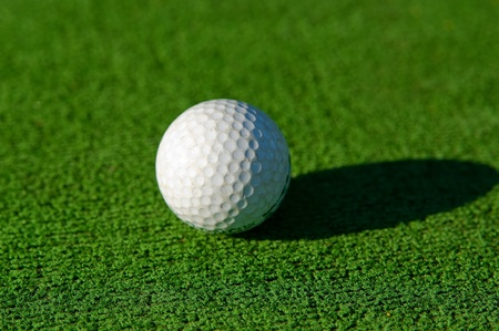 White golf ball lying on a grass Stock Photo