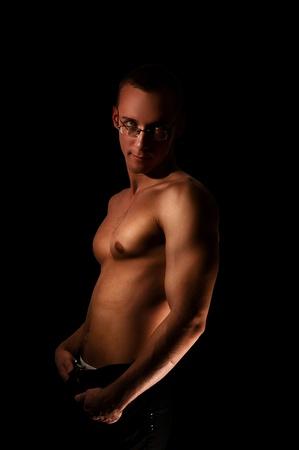 hombre musculoso con m�sculos de socorro aislados en negro Foto de archivo