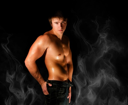 muscular man in smoke isolated on black
