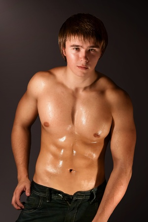 muscle boy: image of muscular man isolated on brown
