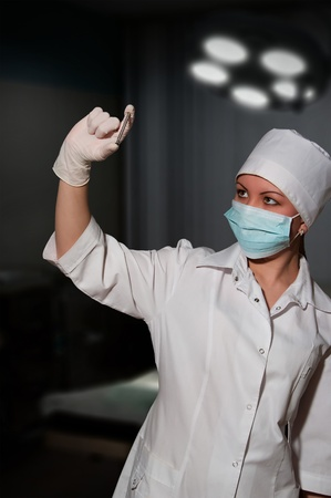 young pretty surgeon holding nail for osteosynthesis in operating room photo