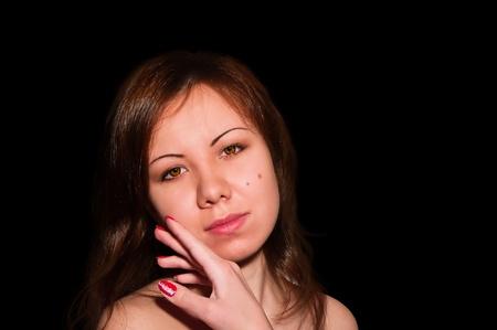 Joven y bella mujer acariciando su rostro limpio belleza aislado en negro