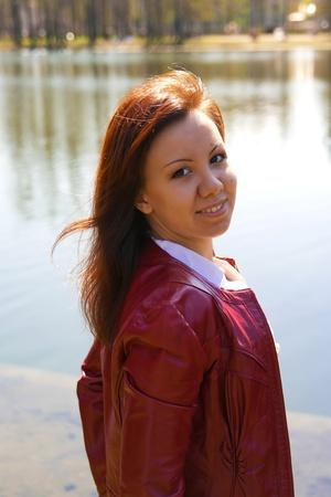 Joven Morena sonriente en la chaqueta de un lago en el Parque