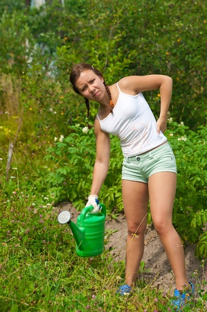 watering pot: Young woman holding watering pot in kitchen-garden and looking tired