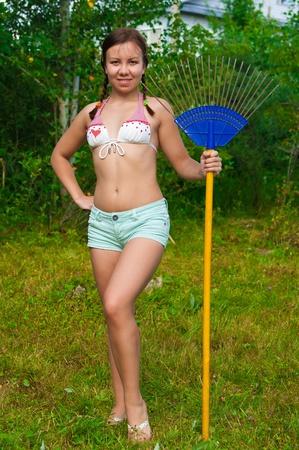 mujer joven feliz rastrillar la hierba en el c�sped. D�a soleado de verano