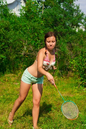girl with racket playing badminton on lawn photo