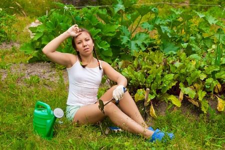 Joven mujer sentada en el suelo en la cocina-jard�n y con aspecto cansado Foto de archivo
