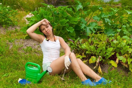 Young woman sitting on ground in kitchen-garden and looking tired photo