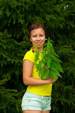 Mujer joven con manojo de ortigas frescas sin guantes