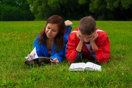 joven est� estudiando un libro mientras chica est� leyendo una revista