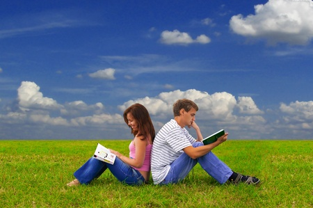 young man is studying a book while girl is reading a magazine Stock Photo