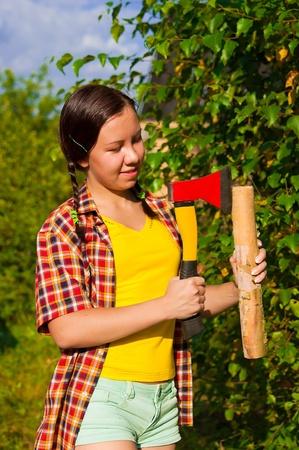 joven mujer que sostiene un hacha y calce en el bosque