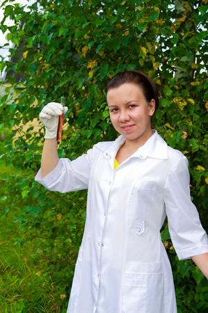 mujer joven médico con el tubo de ensayo con líquidos de color rojo al aire libre