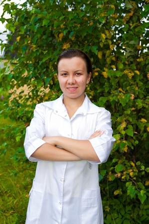 alegre médico mujer sonriente al aire libre en el jardín con los brazos a través de