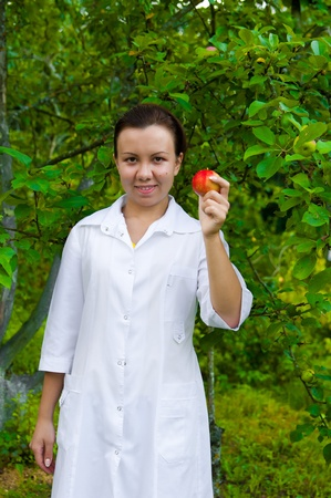 Feliz m�dico sonriente con la manzana en el jard�n con manzanos Foto de archivo