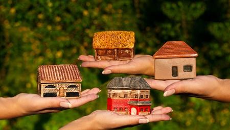 Cuatro casas diferentes en exteriores manos humanas. Concepto de elección