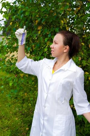Joven médico el análisis de líquido azul en el tubo de ensayo al aire libre Foto de archivo