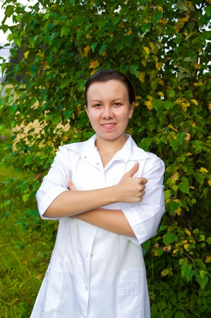 cheerful smiling woman doctor outdoors in the garden with arms across photo
